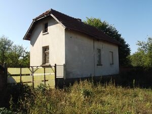 Old house with farm buildings and land in a lively village